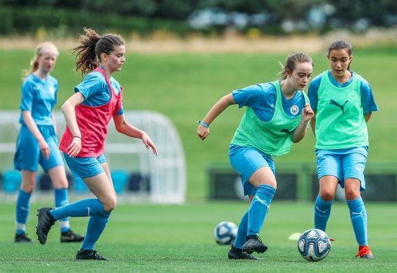 لاعبتان تتنافسان على الكرة في ملعب خارجي بزي مانشستر سيتي في الوقت الذي تنظر فيه زميلات الفريق إليهن في الخلفية