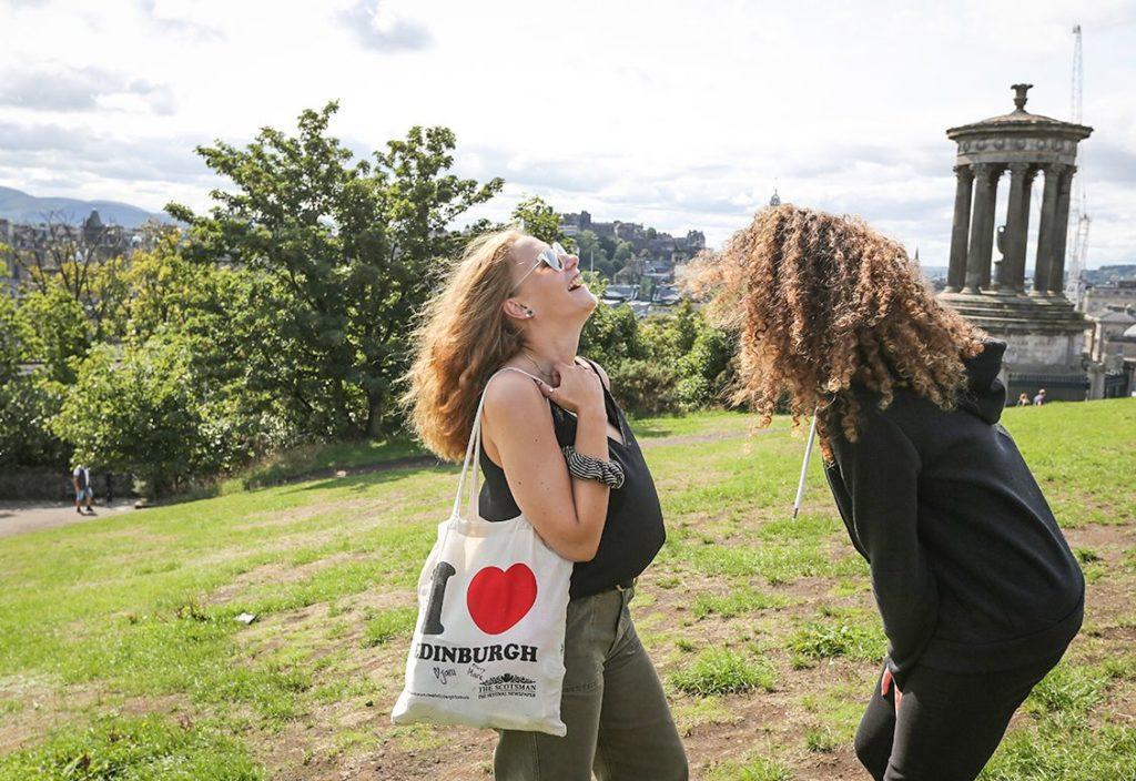 طالبتان تضحكان في الحديقة العامة وتحملان كيس عليه اسم إدنبرة.