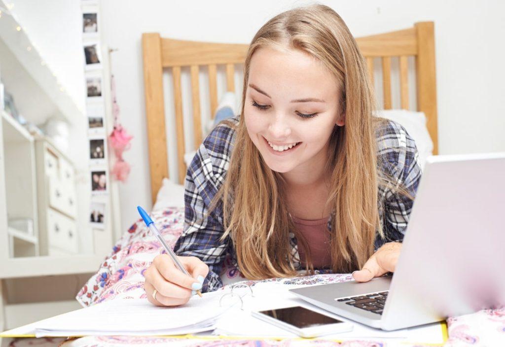 طالبة تدرس في غرفة نوم عائلة مضيفة