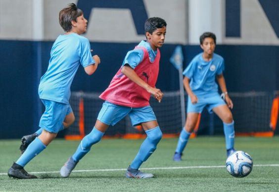 فتيان يلعبون كرة القدم في ملعب داخلي في أكاديمية مانشستر سيتي لكرة القدم