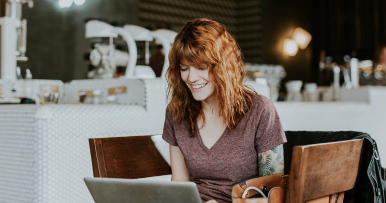Red haired woman using laptop in cafe