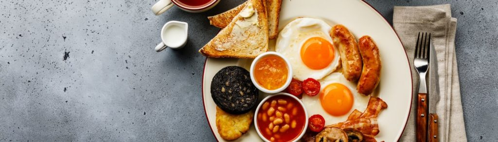 Scottish cooked breakfast with eggs, black pudding, beans, sausages, mushrooms and hash browns