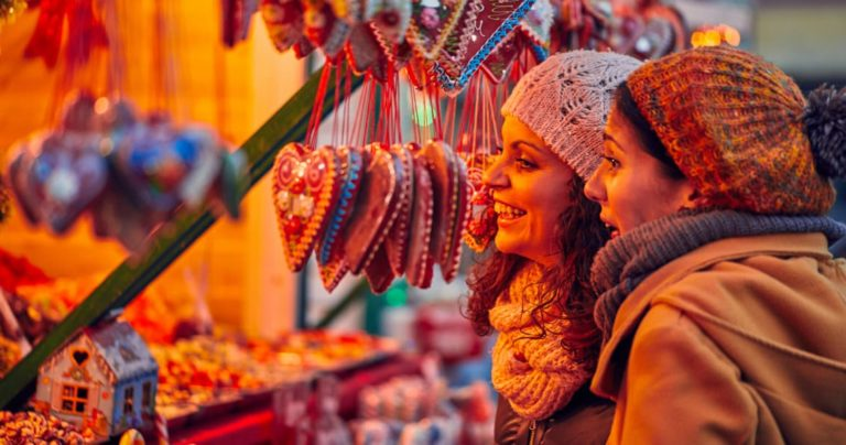 Two women browsing a stall at a Christmas market