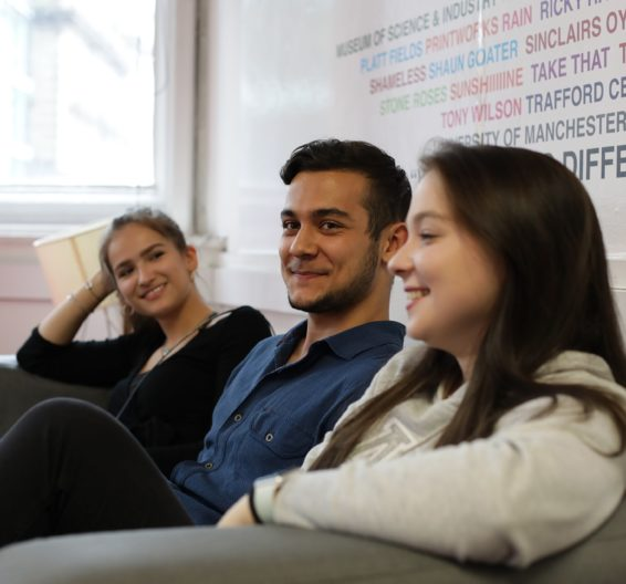 Three students sit on a sofa in BSC Manchester