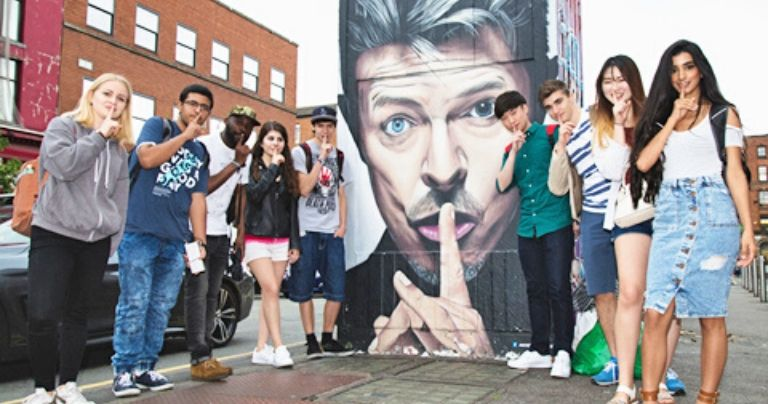 students posing in front of street art in manchester northern quarter