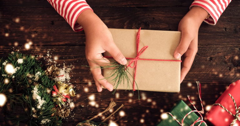 person holding a christmas gift over a wooden table