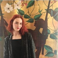 A woman with red hair and a sparkly jacket in front of a floral background in the Ivy toilets