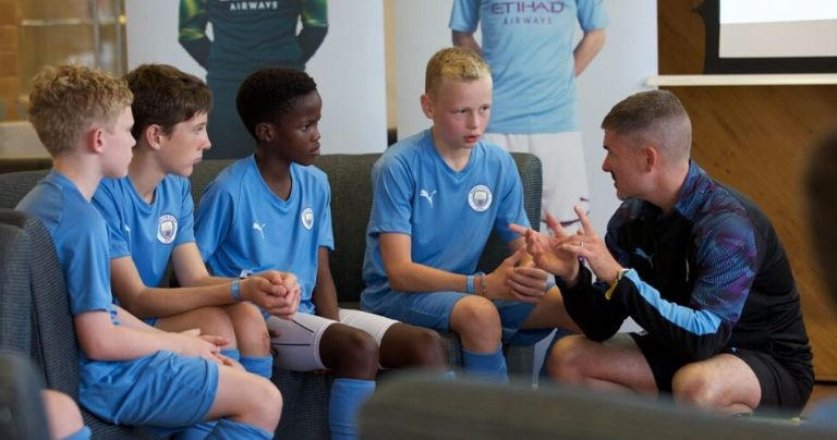Manchester City Football coach training young players in class
