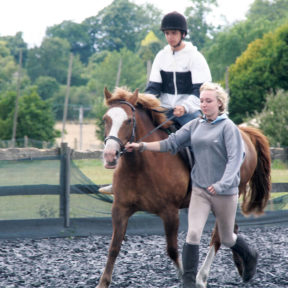 A student on the back of a horse being led across a paddock by an instructor