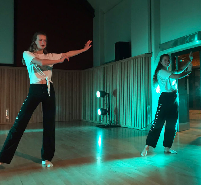 Two girls practise a dance routine in a studio with dramatic green lighting