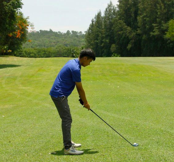 Boy practising golf on fairway