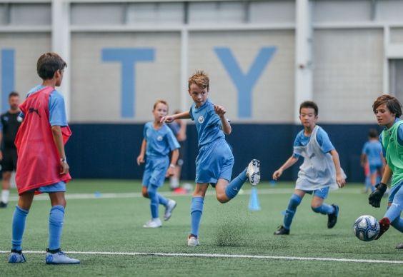 Boy shoots on goal as goalkeeper saves as defenders watch