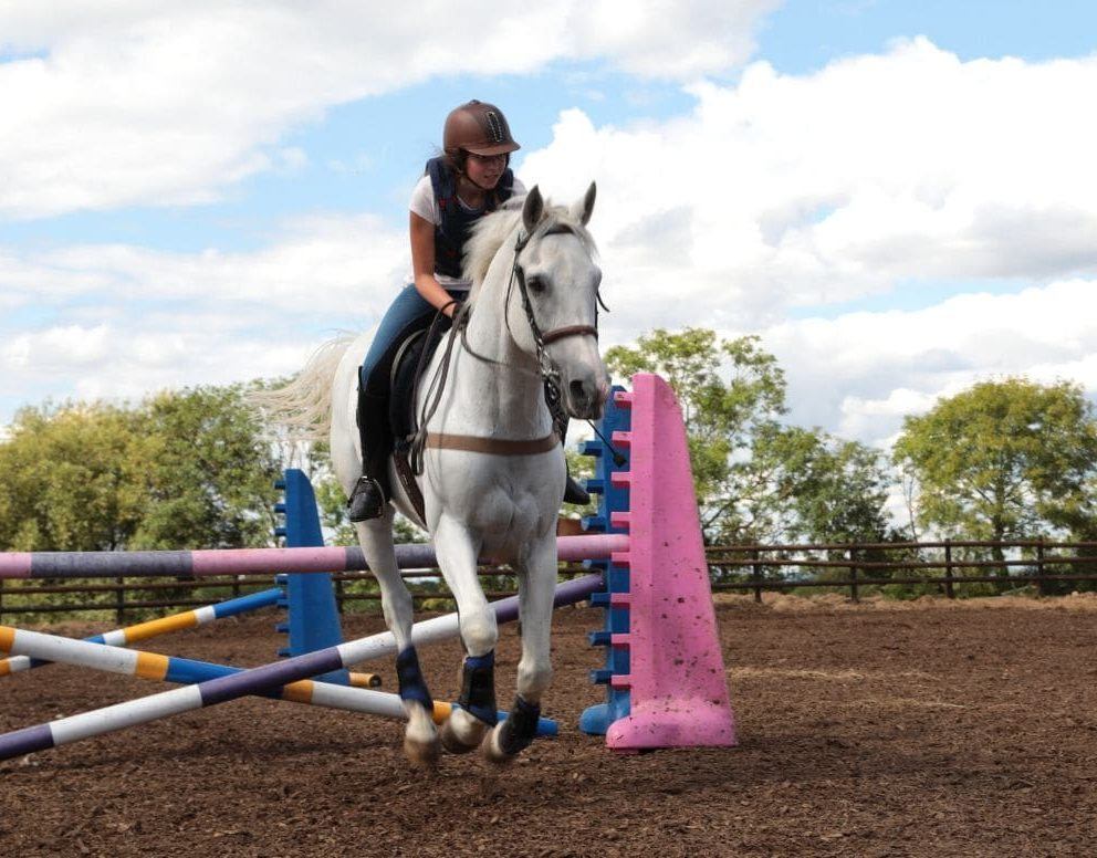 Girl jumping an obstacle on horseback during a horse riding lesson