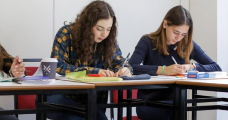Two girls leaning over their desks in a classroom at BSC Dublin