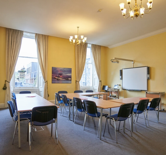 A classroom at BSC Edinburgh with tables and chairs and whiteboard