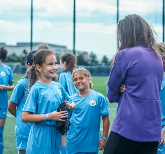 Girls in full Manchester City kit talking with female coaching staff