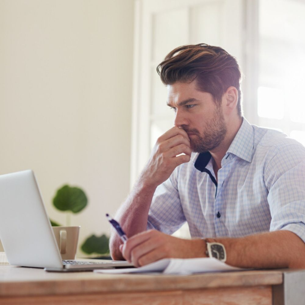 Man sits with coffee cup in front of laptop learning online