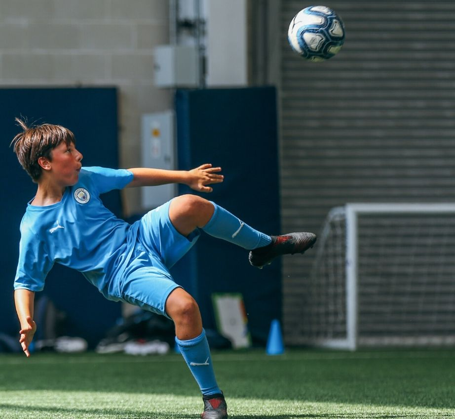 Football player attempting an overhead kick on indoor pitch