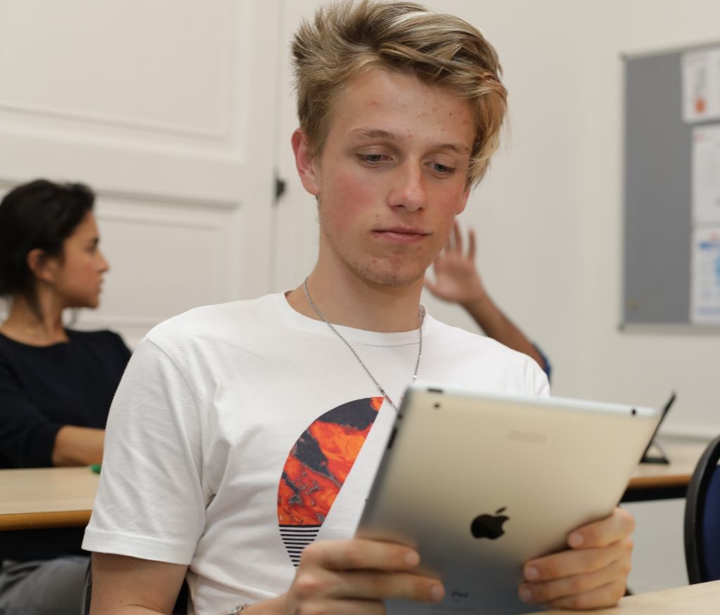 Student in class using an iPad with other students in the background