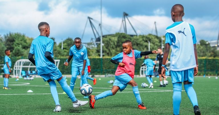 Younger boys football training in Manchester City kit