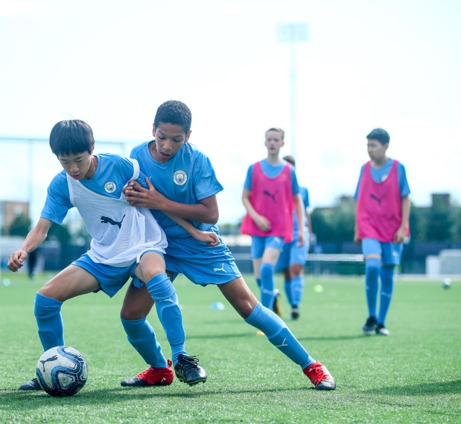 Teenage boys playing football in full Manchester City kit