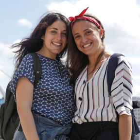 Two smiling students standing outdoors in the breeze