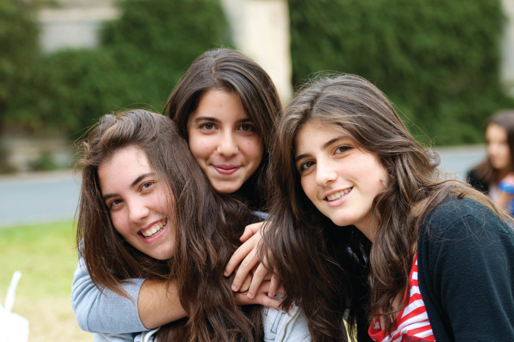 Three young girls hugging outdoors