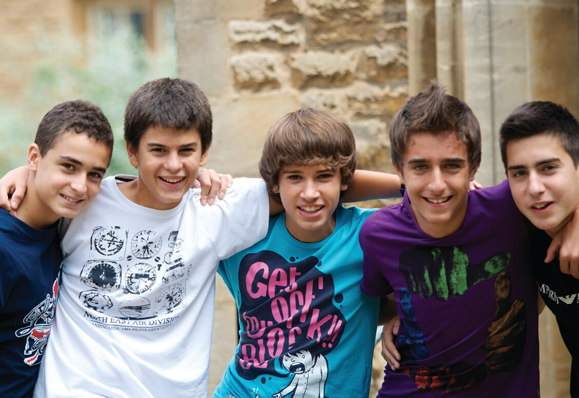 Five boys in bright, youthful clothing face the camera with their arms across each other's shoulders