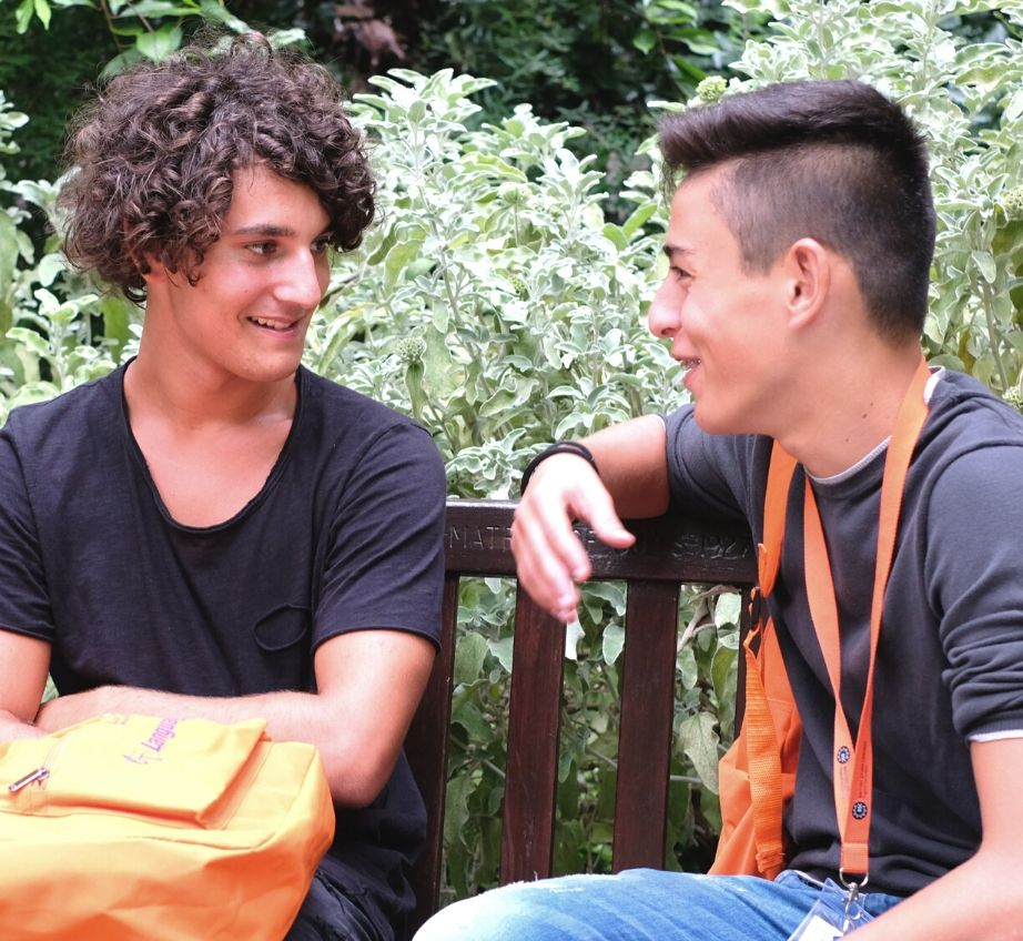 Two teenage boys in dark t-shirts sit talking on a bench