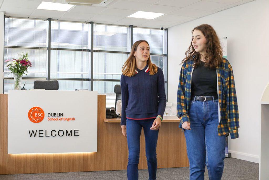 Two teenage girls walk past the modern reception desk at BSC Dublin