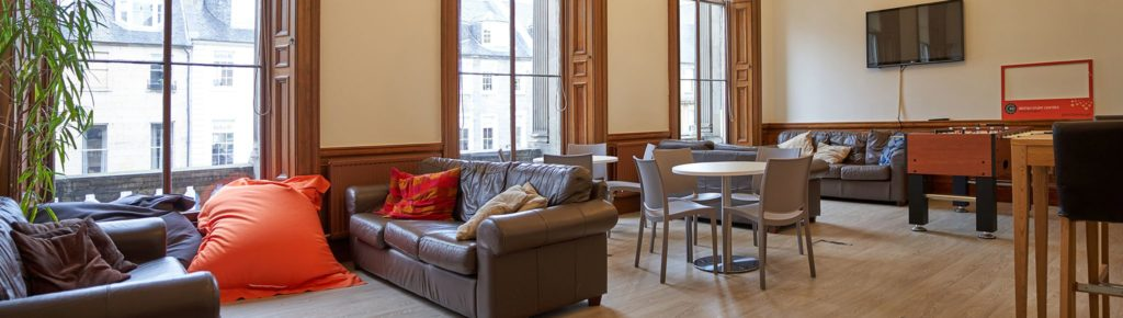 Student lounge at BSC Edinburgh with sofas, TV screen and fussball table