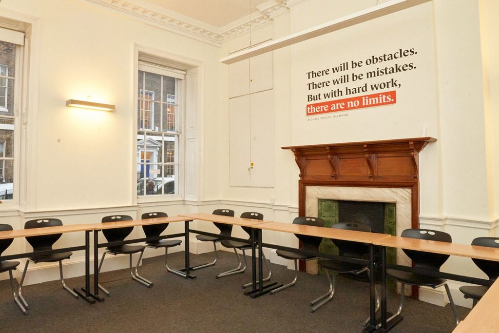 Empty desks in classroom at BSC London with inspirational quote on the wall