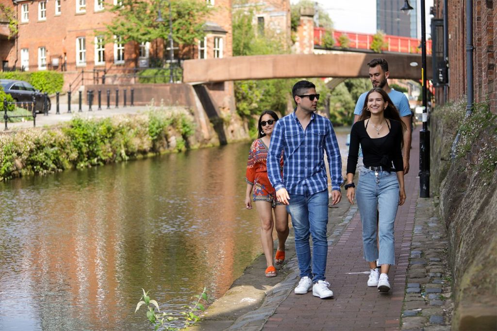 Students walking along a canal in sunny Manchester