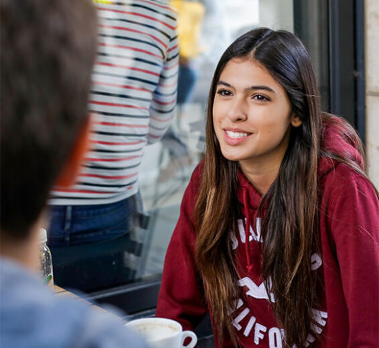 Student smiling sitting outside cafe in conversation with other students
