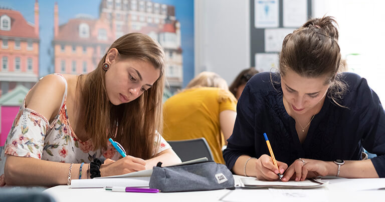 Two students in class taking notes