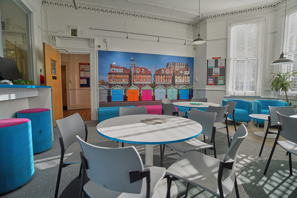 Collaboration hub at BSC Brighton with a picture of beach huts on the wall