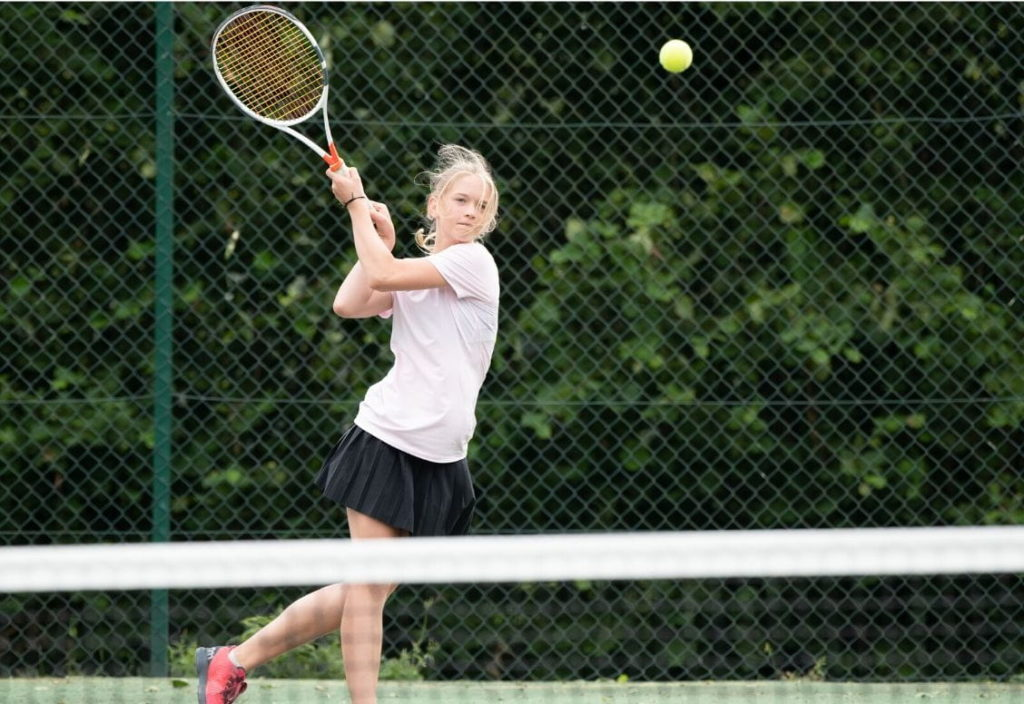 A young student with a tennis racquet focuses on hitting a tennis ball coming towards her