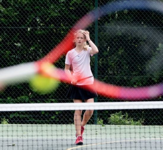 A young girl plays tennis on a court at summer camp