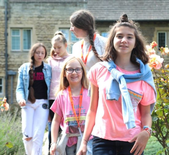 A group of young learners walking through a garden