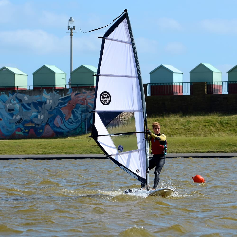 Person windsurfing in lagoon