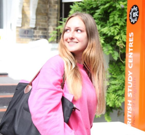 Female student outside BSC Brighton with sign LC Square