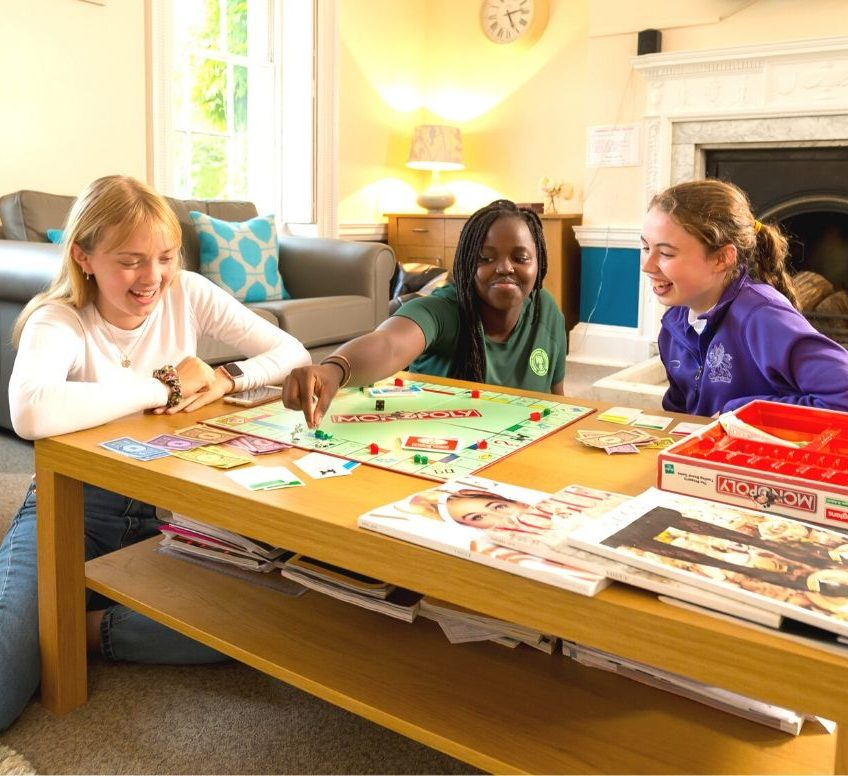 three girls playing a board game around a table