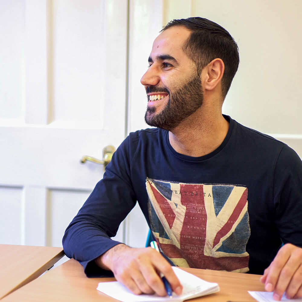 Middle Eastern man learning English with BSC in classroom