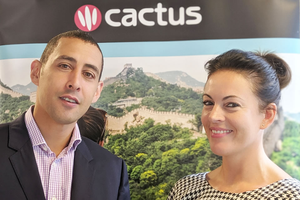 Nick Alexandrou (CEO of BSC) and Faye (Cactus Worldwide) standing in front of the Cactus logo