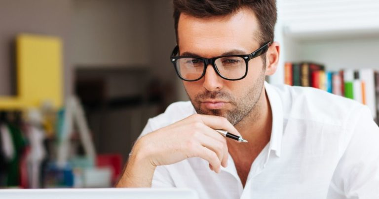 Man in glasses studying intently