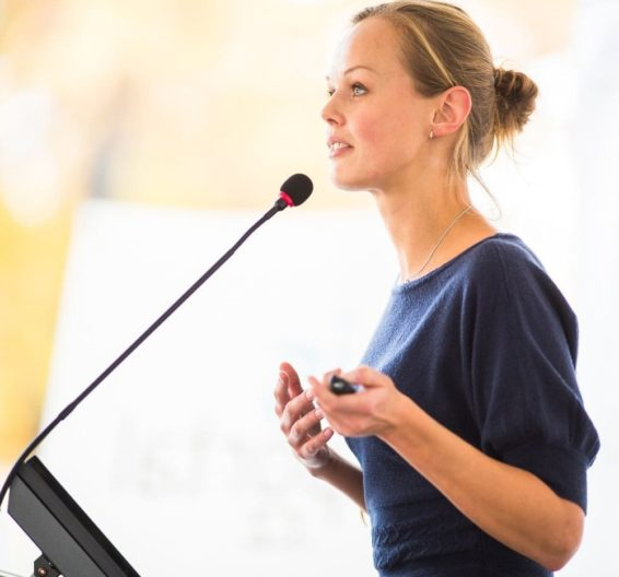 Blonde woman speaking into a microphone