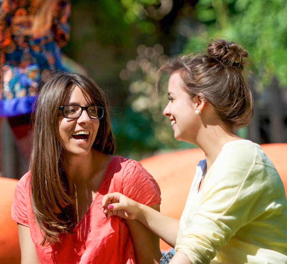 Two young women sit together outside, looking at each other and laughing