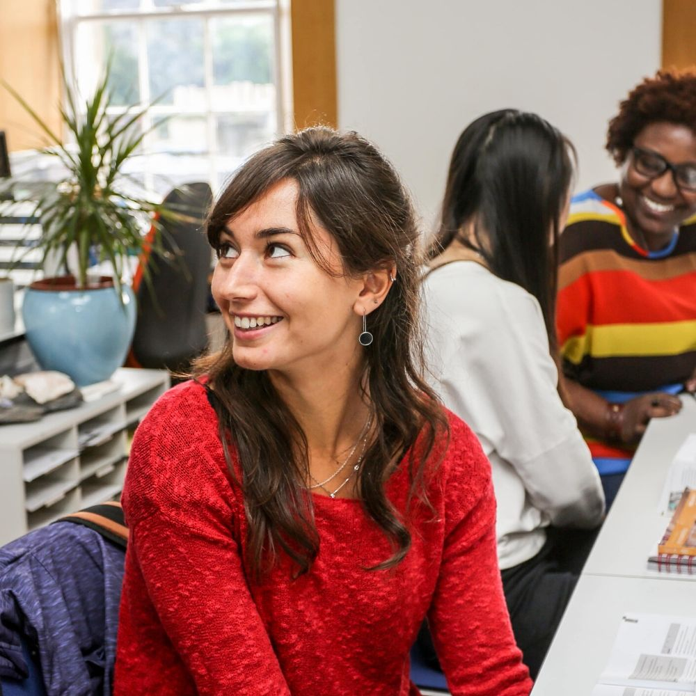 Woman in a red jumper smiling in class