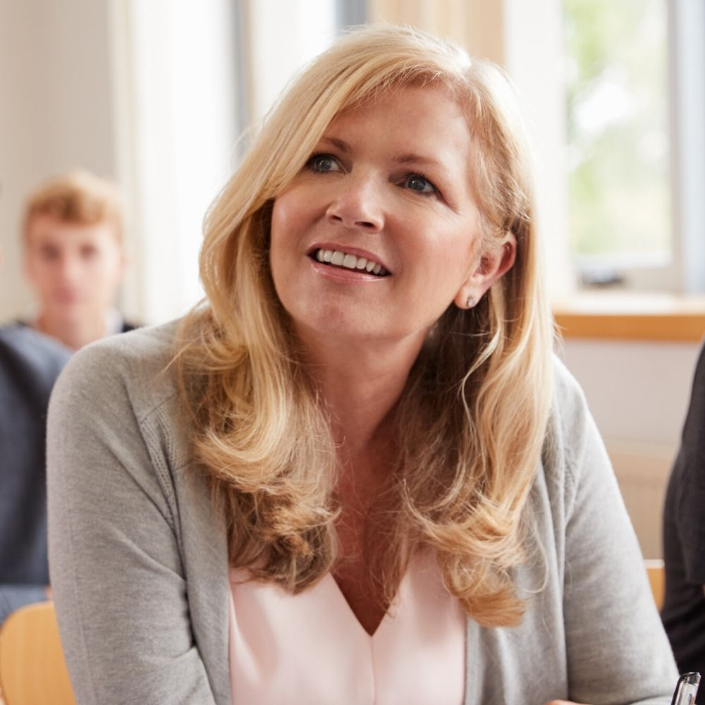 A blonde woman listens in a teacher training session