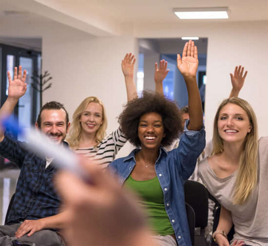 A group of adult students with their hands raised in class